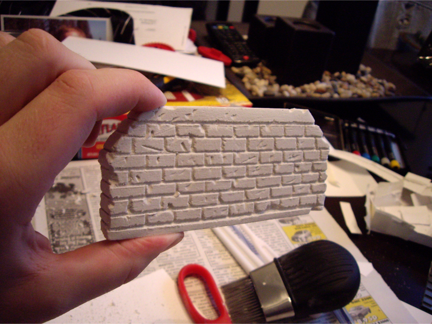 Single plaster bridge abutment made from plaster of paris with carved brick pattern in its face