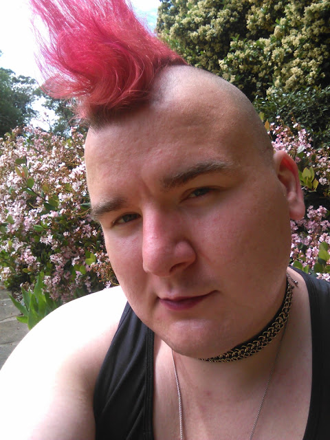 A person in a black tank top and a chain choker with a pink mohawk.