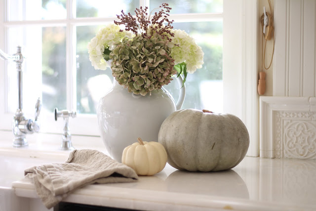 neutral fall decor green and white pumpkins and hydrangeas