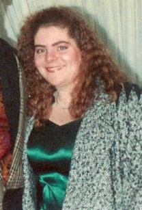 image of me in a green dress and a speckled black and white coat with a perm at age 17