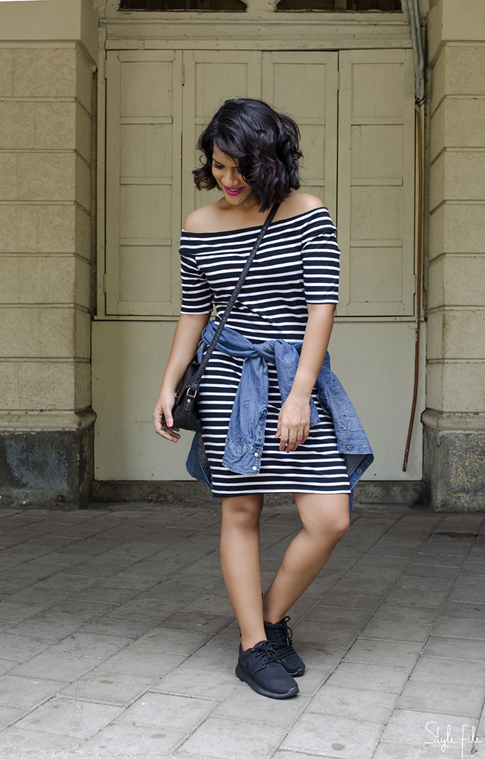 An image of a young woman fashion blogger wearing a striped bodycon river island off shoulder dress, nike rose all black sneakers, denim shirt, accessorize crossbody mini bag and rimmel kate moss pink lipstick with a curly bob hairstyle and pink nails