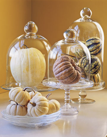 These pumpkins displayed in cake serving trays are a fun autumn decor piece.