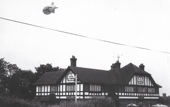 Photograph of Cock O' The North, Great North Road, Bell Bar, with Hartsman advertising airship flying above. July 1985