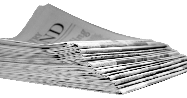 A stacked pile of newspapers from the folded end.