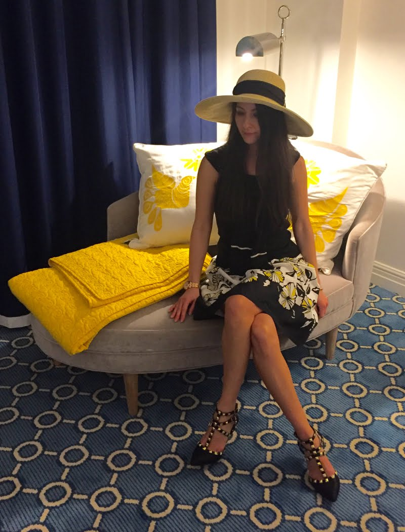 Sitting on a settee wearing a floppy straw hat, black tank top, with a black cardigan around neck, white poofy skirt with black and yellow floral print, and black rockstud heels.