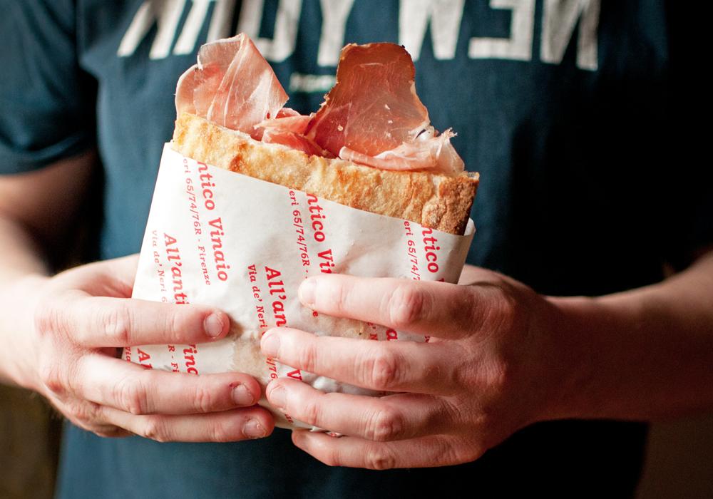 Un homme tient un Sandwich de All'antico Vinaio de Florence. Le sandwich est emballé et du jambon en dépasse.