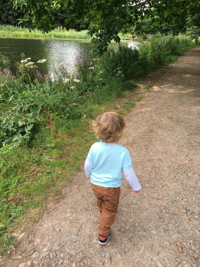 Tredegar-House-&-gardens-a-toddler-explores-toddler-walking-along-side-a-lake