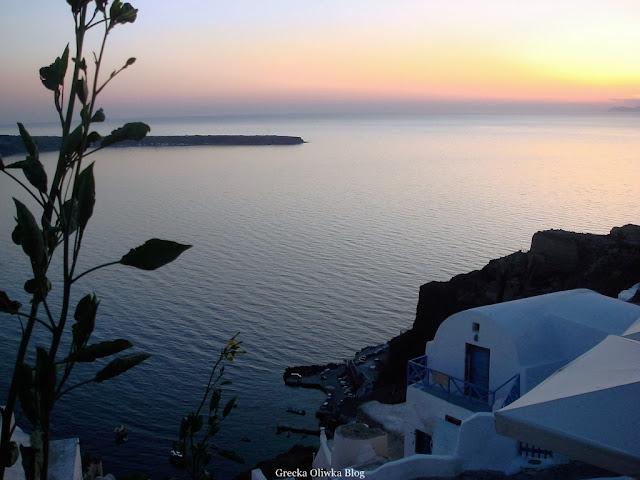 białe greckie domki na tle egejskiego morza oświetlone blaskiem zachodzącego słońca  Fira Santorini Grecja