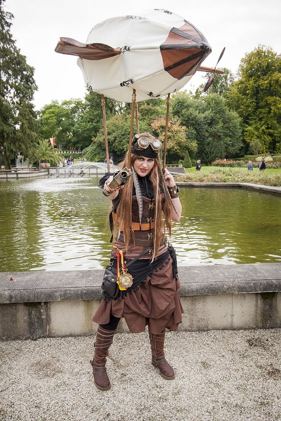 woman wearing a steampunk costume with a ballon/zeppelin/airship tethered above her. She is wearing steampunk clothing and holding a gun.