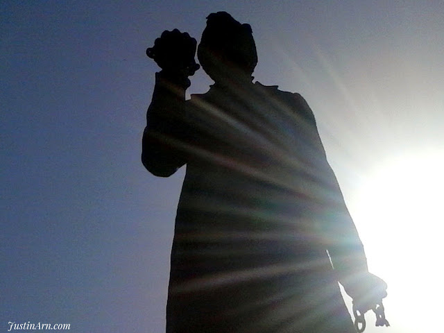 Abraham Lincoln is gripping broken chains with the Sun behind him.