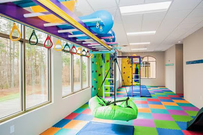 Another view of sensory room with swings and padded colorful flooring