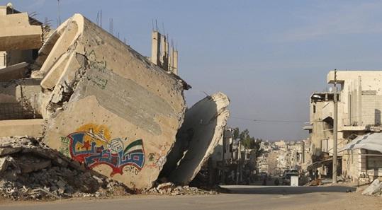 tembok yang dicorat-coret pada bangunan yang rusak di Deraa