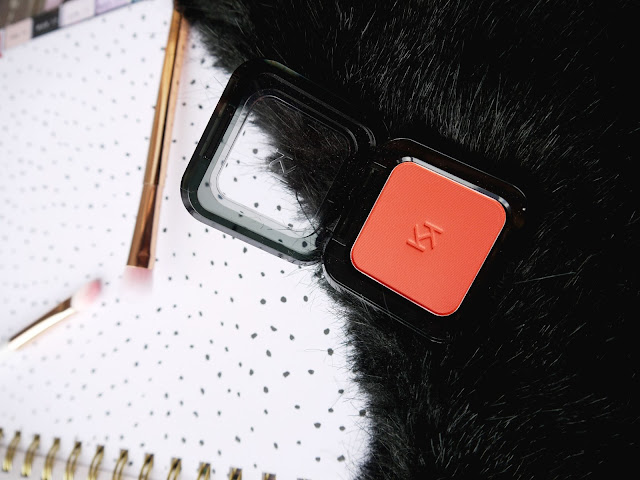 a square compact of red orange eyeshadow sat on a black faux fur background