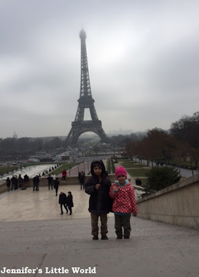 Children by the Eiffel Tower in the mist