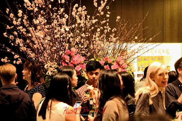Art crowd and Cherry Blossom floral display - Serve the People art opening at White Rabbit Gallery.