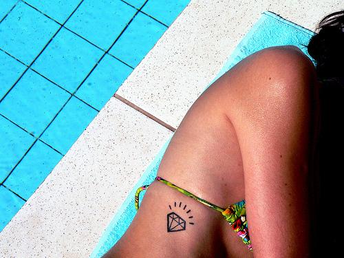 chica en una piscina, esta en bikini, vemos en su costado un tatuaje de diamante