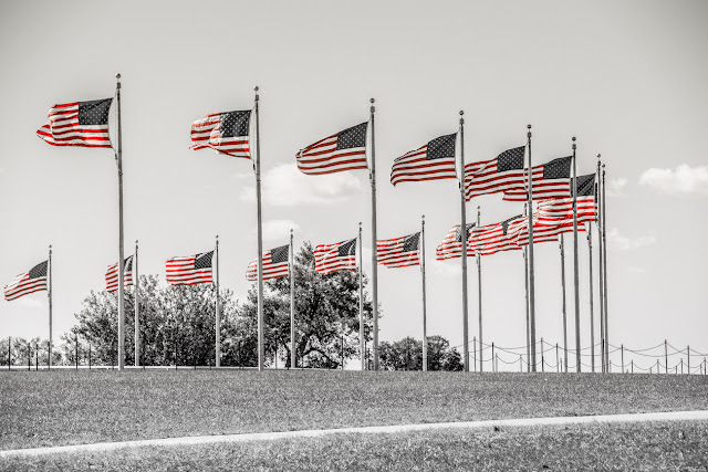 The proud American flag waving in the wind at the base of the Washington Monument in Washington, DC.