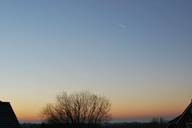 frosty rooftops with sun rising and aeroplane trail