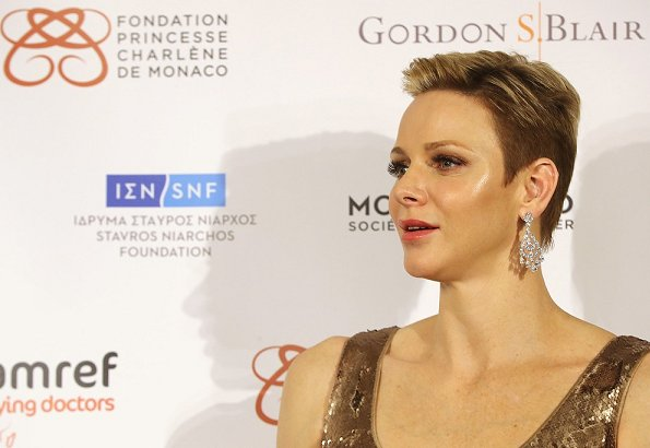 Princess Charlene wore Princess Charlene wore AKRIS Sequined Gown in Gold Metallic at AMREF Gala in evening
