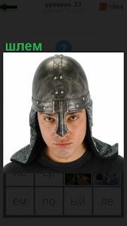 стоит парень, на голове у него одет старинный шлем