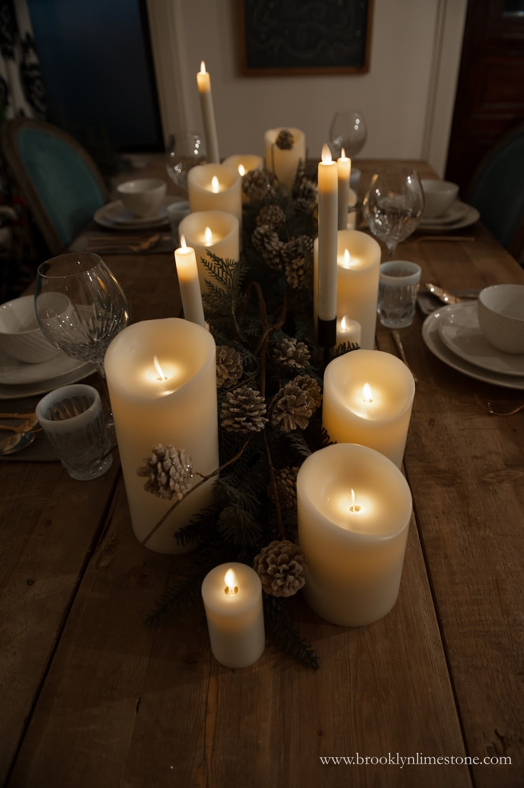 Dining table set with white place settings, flameless candles down the middle and fir branches with pine cones in between them