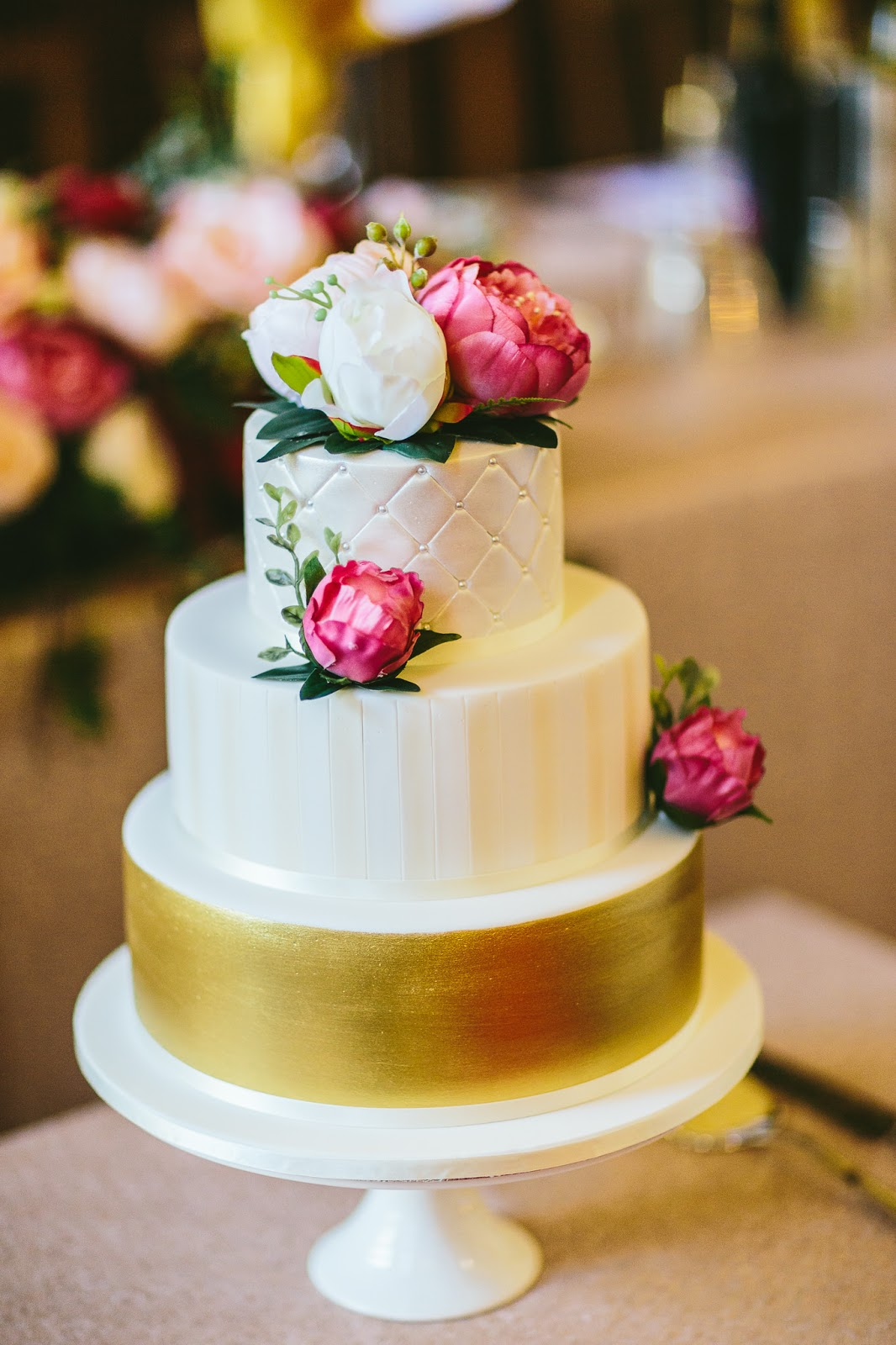 glamorous cake with gold accent and pink flowers