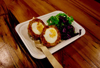 Two semi-circular golden brown scotch eggs showing a white egg with a yellow yolk with pieces of bown chorizo next to a leay green salad on a white rectangular tray on a light brown circular table on a dark background