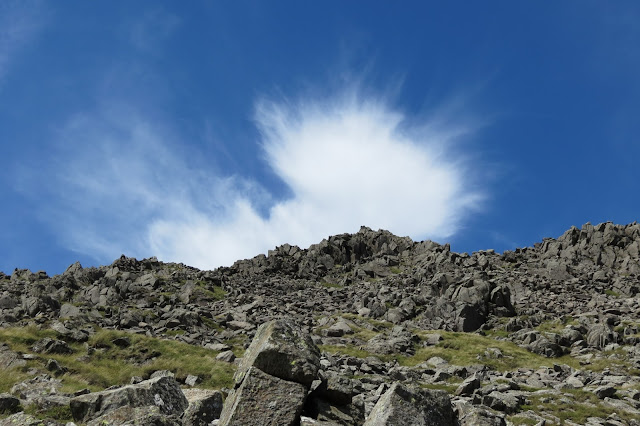 A bright cloud feathering out in the sky above a rocky ridge.