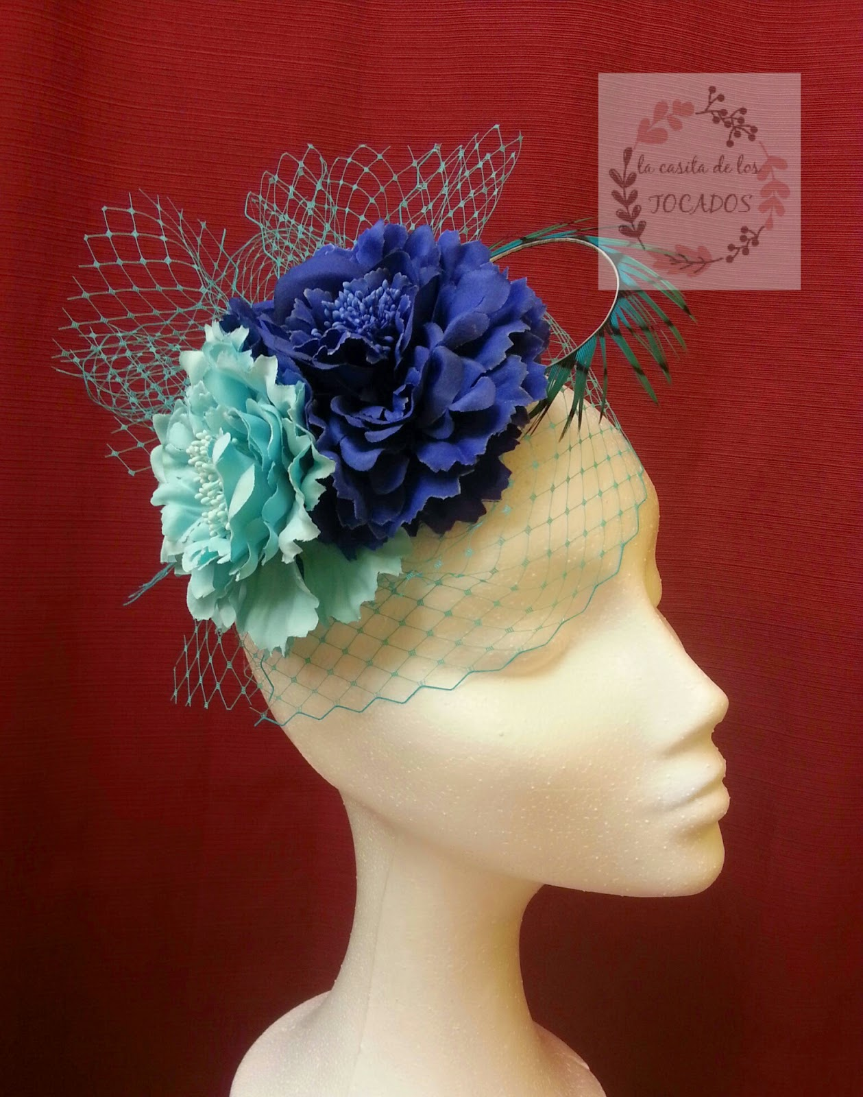 tocado para boda con flores de clavel y velo a la cara en colores azul y turquesa