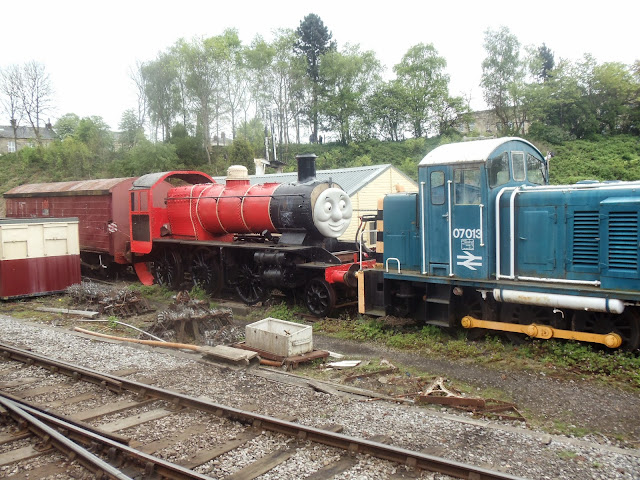 a red engine on train tracks
