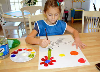 After tracing her hands and then painting the middles of the flowers, Tessa used her freshly mixed green paint to paint stems.