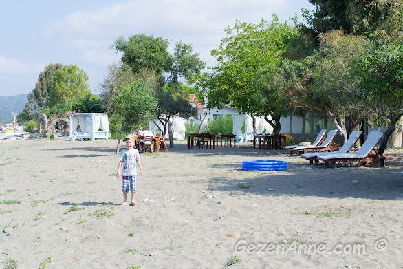 oğlum plajda kumların üstünde çıplak ayak dolaşırken, plajdaki şezlonglar, masalar, yastıklar, Yonca Lodge Fethiye