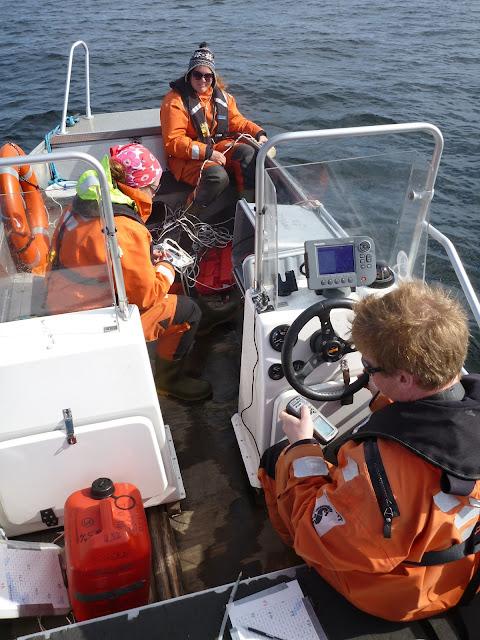 Kolme pelastautumispukuista henkilöä veneessä