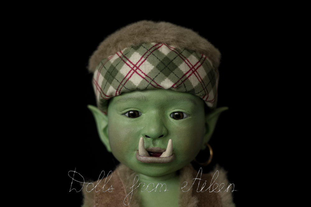 ooak artist baby orc doll looking into the camera