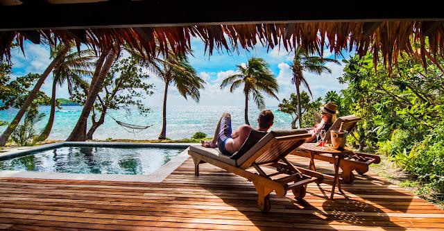 Couple sur chaise longue face à la mer, proche piscine