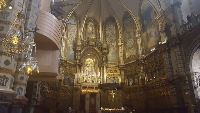 An ornately decorated cathedral wall, draped in gold furnishings and intricate artwork, including the statue of the Virgin of Monsterrat
