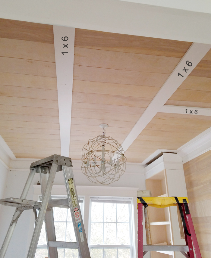 dining room with two ladders, big sphere chandelier and plank ceiling