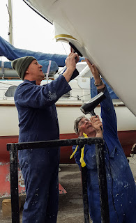 Photo of Phil and Tony putting up the new bow logo