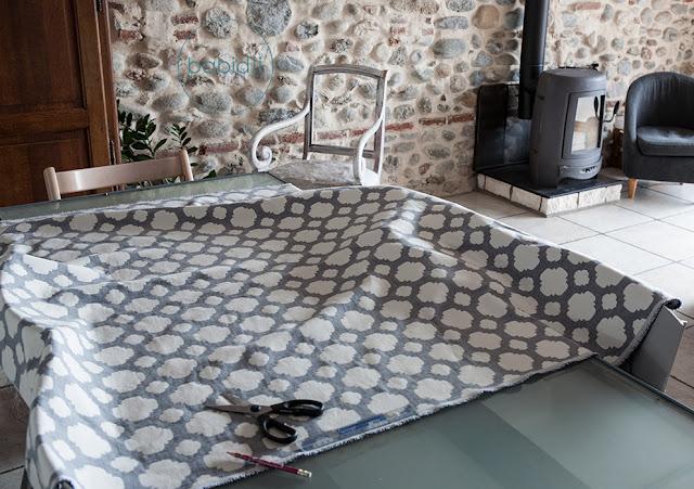 tissu sur une table prêt à être découpé pour tapisser un fauteuil
