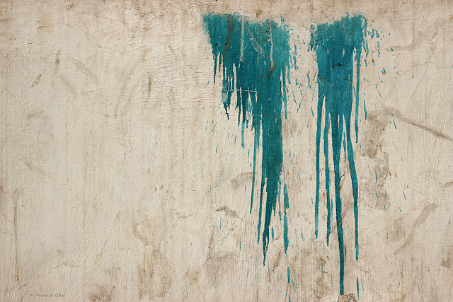 A Minimalist Photo of Two patches of dripping blue paint on a textured Indian wall