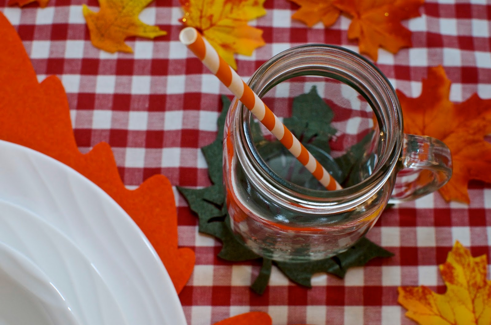 Mason jar glass, orange and white straw, checked tablecloth.