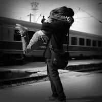 Bir tren garında erkek arkadaşının kucağına atlayarak sarılmış bir kız