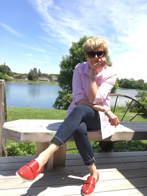 woman in pink shirt, jeans, and red loafers on a deck with river behind