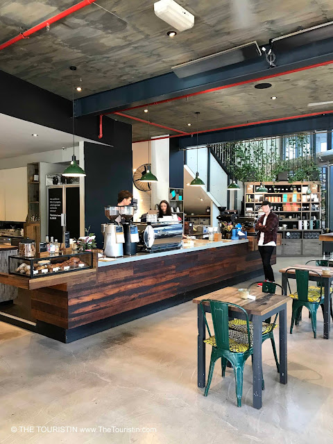 Green chairs with colourfull cushions, concrete floor and a large wooden cafe counter