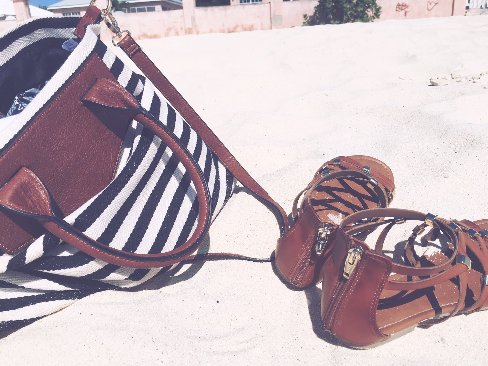 Striped beach bag and brown strappy sandals on sand of Grand Turk, Turks & Caicos beach