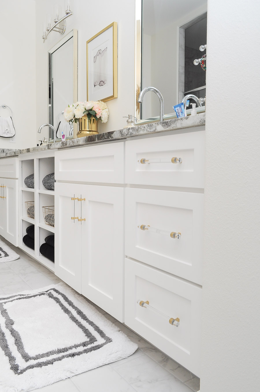 White shaker cabinet vanity with open shelving for towel storage. This master bathroom suite is gorgeous- I am loving all the gold, chrome and glam decor.