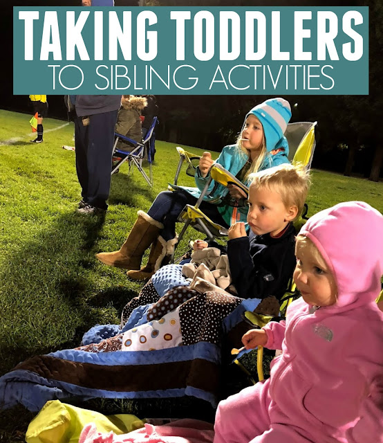 four kids watching a soccer game sitting on camping chairs covered in blankets
