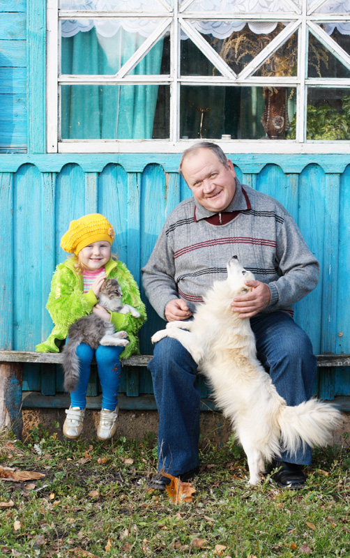 A man with his grand-daughter, little dog and cat, seated outside