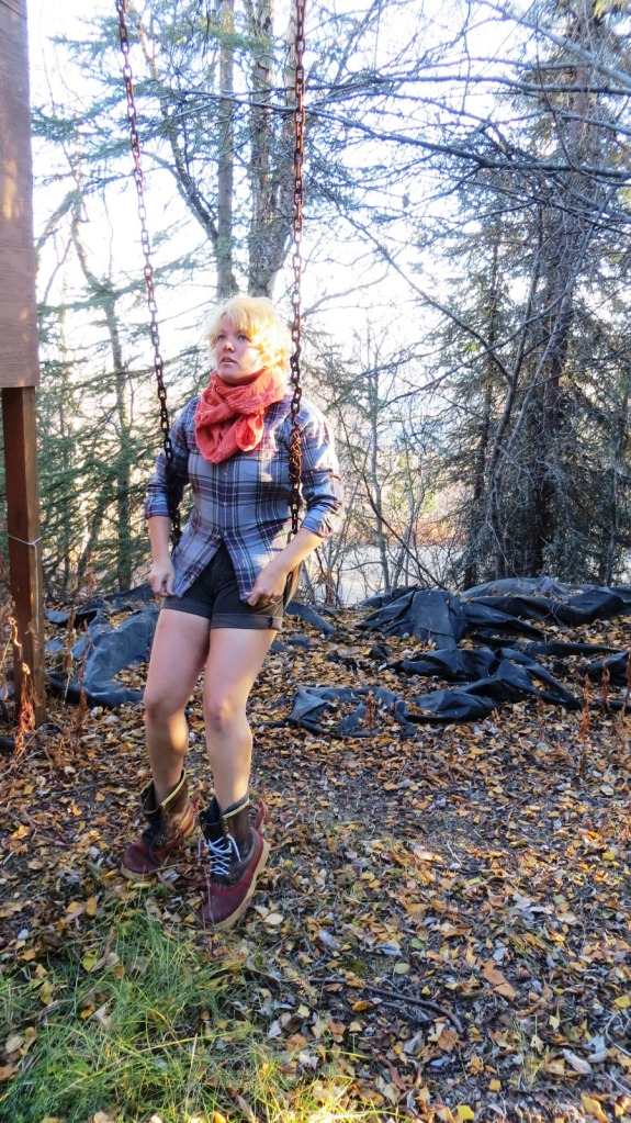 Kface in flannel and workboots on a swing set in the woods