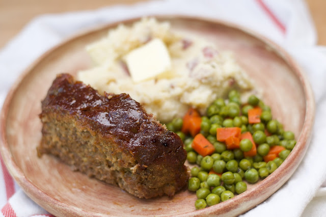 A slice of the finished meatloaf on a plate with mashed potatoes and peas and carrots.